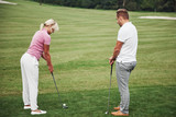 Girl playing golf and hitting by putter on green. Her teacher helps to explore the technique and make her first strikes - 244205660