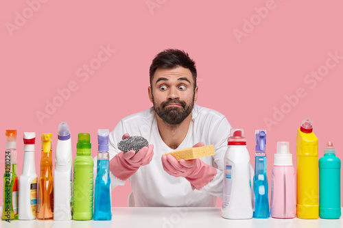 Leinwandbild Motiv Indoor shot of surprised bearded man looks with eyes popped out, wears casual clothes, uses different detergents, isolated over pink background, prepares for washing dish. Apartment cleaning