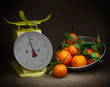 Oranges, tangerines on scales on rustic hessian. Dark, chiaroscuro style still life. Vintage theme.
