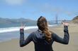 Segno della vittoria di ragazza dalla spiaggia al cospetto del Golden Gate