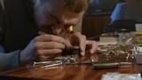 portrait of a watchmaker in a special magnifying eyepiece. Man repairing mechanical watches - 244232660
