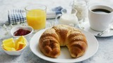Served breakfast with baked golden croissant and jam with glass of orange juice on marble table - 244254848