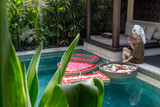 A woman in bathrobe sitting next to the pool, having romantic floating breakfast with I love you flower arrangement, anniversary, valentine or birthday celebration concept - 244256023