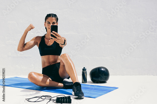 Wall mural Fitness woman taking a selfie during workout