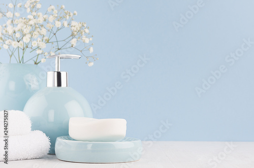 Light pastel blue acessories for bath and skin and body care product - soap, soap dispenser, towel on white wood table. Decor for bathroom interior.