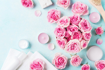 Aromatherapy, spa, beauty background with roses flowers, cosmetics and candles on blue table. Flat lay style.