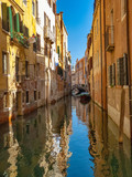 small canal in the city of venice with narrow houses - 244290261