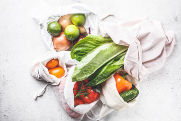 Vegetables in eco cotton bags, pepper, tomato, lettuce, cucumber, lime, onion. Zero waste food shopping.