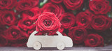 Concept Valentine day, love, machine transports a flower on the background of red roses. Stylish love concept, space for text.