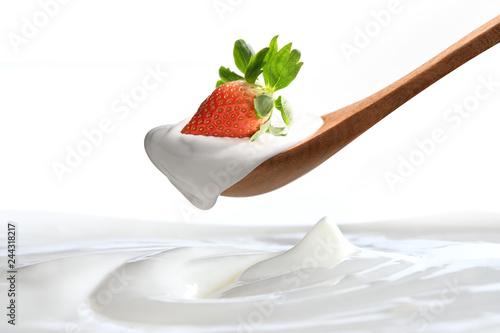 Leinwandbild Motiv Plain yogurt on a spoon with fresh  strawberry on top hanging above of plain yogurt isolated on white background
