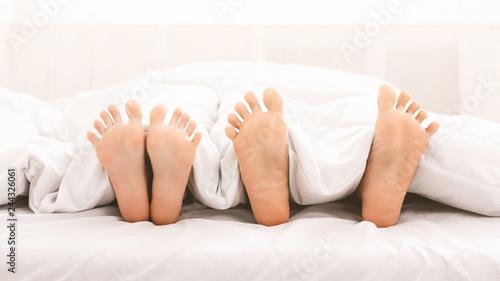 Leinwanddruck Bild Feet of couple in bed under blanket