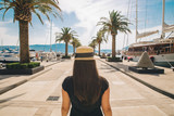 woman walk by sunny pier with palms. mountains and yachts on background