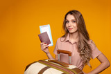 Portrait of a cheerful young woman dressed in summer clothes holding passport with flying tickets while standing with a suitcase and pointing finger away isolated over yellow background - 244368694