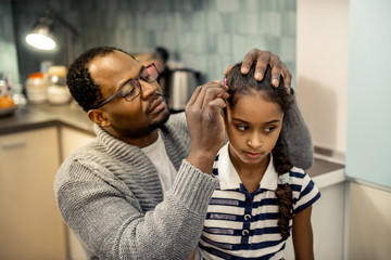 Father wearing grey cardigan fixing hairstyle of his daughter © Viacheslav Iakobchuk