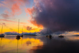 Sunrise on the lake with boats, reflection of sun in water, with fog and clouds on summer morning