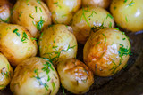 Baked potatoes - jacket potatoes - whole in their skins with sunflower oil and dill until golden brown . Close up. - 244392878
