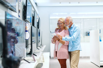 Married senior couple looking at specifications for television set they want to buy. Tech store interior.