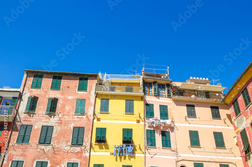 Poster View on the beautiful colourful houses with clothes drying in the sunny daylight in Cique Terre, Italy.