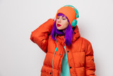 Portrait of a beautiful girl with purple hair in orange hat and jacket and with headphones on white background. Trendy style