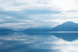 Mountains silhouetted against clouds and mist with sky reflection on calm lake