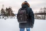 tourist stands with a backpack in the winter forest and looks into the distance