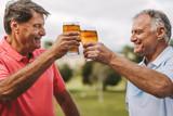 Senior men celebrating with beers