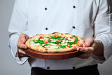 Italian man chef cook holding a finished pizza on a gray background. Cook in jacket with a ready dish. Italian food. profession image. Free copy space for logo or text - 244470848