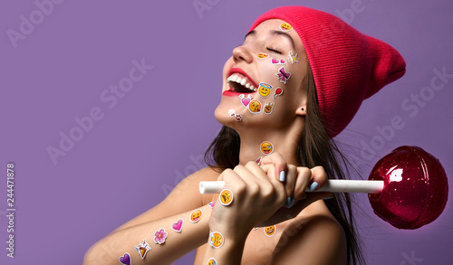 Brunette woman with popular social emoji smiles stickers on her face and hands happy smiling laughing hold big sweet lolly pop candy © Dmitry Lobanov