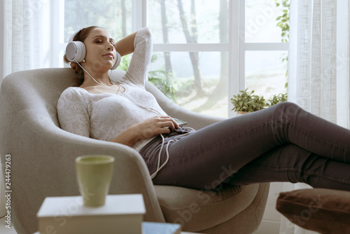 Woman listening to music with eyes closed - 244479263