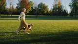 Active woman runs with the dog in the park - 244487453