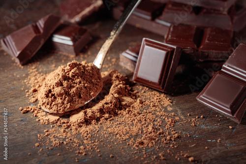 fototapeta na ścianę Broken chocolate pieces and cocoa powder .