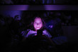 Leinwanddruck Bild Little girl at night under a blanket looking at the smartphone.
