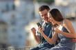 Leinwandbild Motiv Excited couple celebrating online phone news outdoors