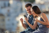 Excited couple celebrating online phone news outdoors - 244528028