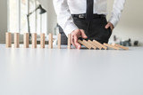 Fototapeta Panele - Front view of business consultant stopping falling dominos © Gajus