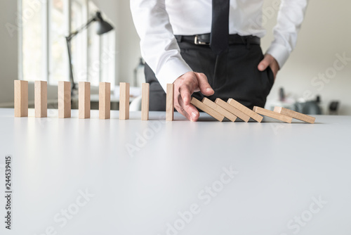 Front view of business consultant stopping falling dominos