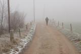 woman walks on a rural trail on a foggy winter day - 244542473