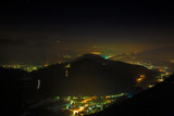 Fototapeta Miasto - Panoramic night view from above, of the city lights, with low polluted atmospheric layers. © serghi8