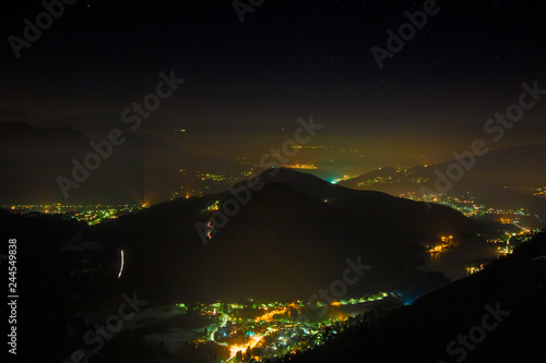 Panoramic night view from above, of the city lights, with low polluted atmospheric layers.