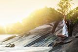 Fototapeta Zachód słońca - Woman Yoga Meditates on a Rock on the Ocean Beach in the Sunlight © Maksim Pasko