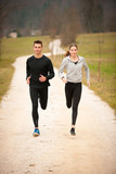 Young  veautiful couple runs on a path in park on autumn afternoon - 244550053