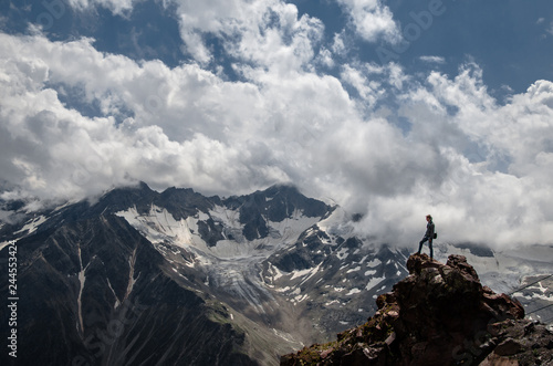 a young man stands on a rock against the backdrop of high mountains