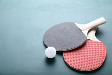 Table tennis rackets with ball on green background