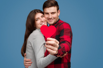 Cheerful couple showing small heart