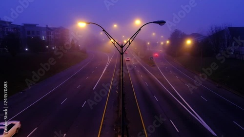 Slow motion footage of road car traffic at foggy night modern city