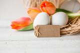 Fototapeta Tulipany - Ostern - Orangefarbene Tulpen im Nest auf hellem Grund und Anhänger  © sc Fotografie