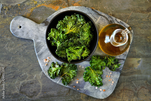 Platter of healthy kale chips. Top view, on a dark slate background.
