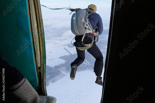 A paratrooper is jumping out of a plane. - 244574418