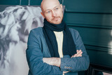Portrait of attractive adult successful bald man art critic historian with beard in scarf in art gallery - 244582495