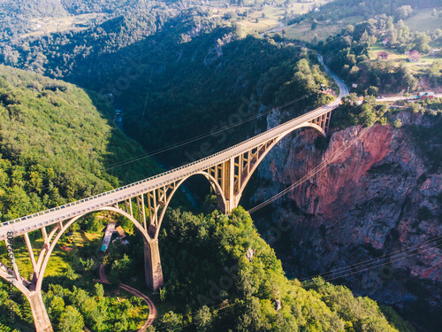 Wall mural highway with high bridge cross canyon. blue clear water